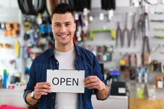 Bike shop owner holding open sign Royalty Free Stock Images