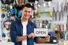 Bike shop owner holding open sign Stock Photos