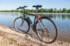 Bike on the shore of crystal clear lake Royalty Free Stock Photos