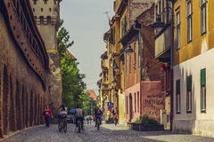 On bike in Sibiu city, Romania. Unidentified tourists enjoy a city tour on bike along the medieval fortified wall with defense towers on 06 May, 2015 in upper Stock Photos