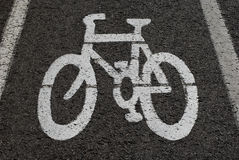 Bike sign. Painted sign of bicycle painted on the road black background Royalty Free Stock Photography