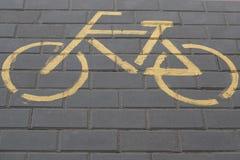 Bike sign yellow paint on the street. Description: Bike sign yellow paint on the street, asphalt, bicycle, biking, city, path, road, safety, sport, symbol stock image