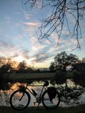 Bike Silhouette on Lake at Sunset. Vertical of bicycle silhouette with lake and sky at sunset in background Stock Photo