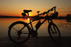 Bike silhouette on sunset. Silhouette of the bicycle standing near the lake. Sunset Royalty Free Stock Photo