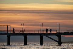 Bike, singles and a couple`s silhouettes on the pier. With sunset background Royalty Free Stock Image