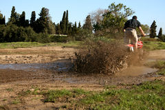 Bike Splash. Young biker on an off road bike riding through a puddle of water Royalty Free Stock Photography