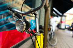 Bike stands with a headlamp at the window in the city Royalty Free Stock Image
