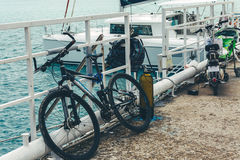 Bike stands on a pier against the background of a sailing yacht on azure sea water Stock Photography