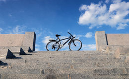Bike stands on the stone steps on the background of blue sky and Stock Photography