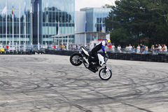 Bike stoppie motorcycle stunt rider acrobatics. This motorcycle stunt rider is making acrobatics stoppie on dirty asphalt, near office buildings stock photo