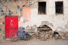 Bike on street. A blue bike stands in front of red door in street Royalty Free Stock Image