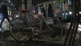 Bike in street of night winter city. People and transport traffic in background