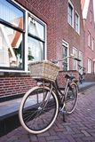 Bike on a street. Retro bike with basket standing on a street of amsterdam Royalty Free Stock Images