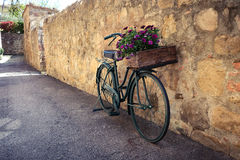 Bike on a street. Retro bike with flowers standing on a street of small italian town Stock Photos