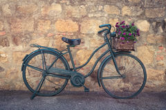 Bike on a street. Retro bike with flowers standing on a street of small italian town Royalty Free Stock Photography