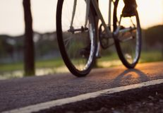 Bike at the summer sunset on road in city park. Cycle closeup wheel on blurred light at summer. stock photo