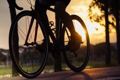 Bike at the summer sunset on road in city park. Cycle closeup wheel on blurred light at summer. royalty free stock photography