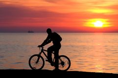 Bike on sunset. Biker watching sunset on the black sea Royalty Free Stock Photos