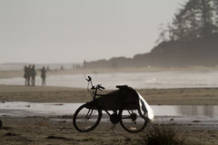 Bike with Surfboard Cover on Beach. An empty surfboard cover resting on a bike parked on a sandy beach Royalty Free Stock Photo