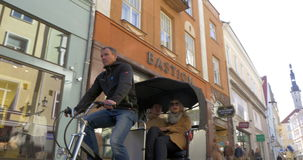 Bike Taxi Riding in Tallinn. TALLINN, ESTONIA - APRIL 27, 2015: Steadicam shot of a bike taxi carrying two tourists along the streets of Tallinn stock footage