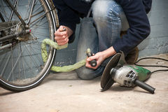 Bike theft. Thief opening the lock of a bicycle with a portable grinding machine Stock Photo