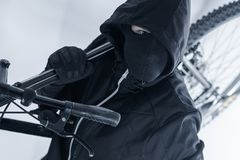 Bike Theft. Bike Thief in a Hood, Black Mask and Black Gloves. Caucasian Male Thief royalty free stock photo