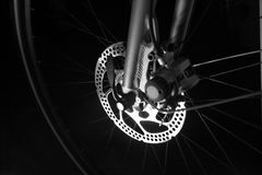 Bike tire, rim, spokes and disc brake hub. Front tire on a bike on black background, showing tire, rim, spokes and shinny disc brakes - an alternative form of stock image