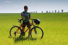 Bike tourist. Young Biker tourist relaxation in green field Stock Image