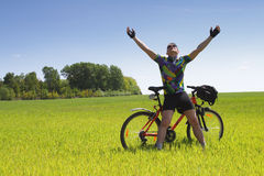 Bike tourist. Young Biker tourist relaxation in green field Royalty Free Stock Photography