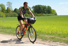 Bike tourist. Young man bike riding in the field Royalty Free Stock Photos
