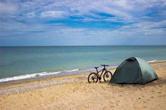 Bike and tourist camp on a sunny seashore Royalty Free Stock Photo