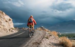 Bike tourist rides on Himalaya mountain road on way to buddist m Stock Image
