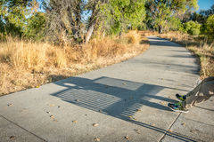 Bike trail with a shadow of man resting on a bench Royalty Free Stock Photography