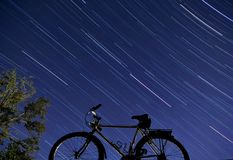 Bike and tree under stars. Bicycle and tree at night with stars streaking in sky Royalty Free Stock Images