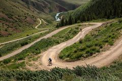 Bike trip. A man with a bicycle on a mountain pass. Kyrgyzstan stock image