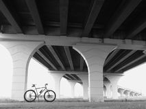 Bike Under Bridge black and white. Black bicycle on left with bridge receding to the right in background Stock Photo