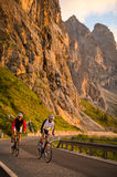 Bike uphill by sunset - sunrise. A couple take a ride by sunrise - portrait format Royalty Free Stock Photo