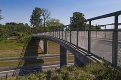 A bike and walking bridge. A bridge for pedestrians and bicykists to cross the road below on Royalty Free Stock Images