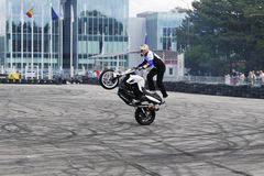 Bike wheelie motorcycle stunt rider acrobatics. This motorcycle stunt rider is making acrobatics wheelie on dirty asphalt, near office buildings Royalty Free Stock Image