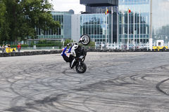 Bike wheelie motorcycle stunt rider on tarmac. This motorcycle stunt rider is making a slow wheelie on dirty asphalt, near office buildings Stock Photos