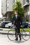 On the bike wherever I want!. Full length of young businessman rolling his bicycle while crossing the road Royalty Free Stock Photography