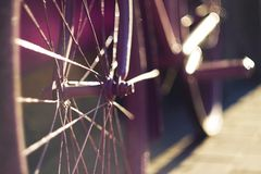 Bike, whose spokes shine in the rays of the sunset. Beautiful purple retro bike, whose spokes on the wheel shine brightly in the rays of the sunset stock images