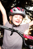 Bike Winner Victory. A preteen boy at dusk with bike helmet showing victory expression. Shallow depth of field Stock Photography
