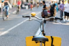 A bike with a yellow bell on its handlebar parked in the sidewalk in Amsterdam city center royalty free stock photography