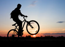 Biker. Boy on a bicycle in the sunset Stock Photo
