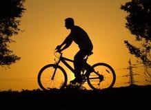 Biker. Black biker silhouette on orange sunset Stock Photos