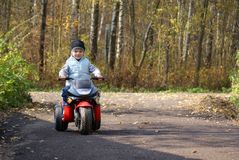 Biker. Young boy 6 years old driving toy motorbike Royalty Free Stock Photo