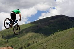 Biker. A competitor scouts his landing from the air after performing a trick during the 2010 Teva Mountain Games Slopestyle event held in Vail, Colorado Royalty Free Stock Photos