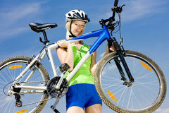Biker. Woman biker carrying her bicycle Stock Image