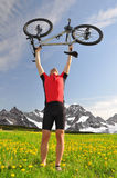 Biker. With the mountain bike in the dandelion field Royalty Free Stock Photo